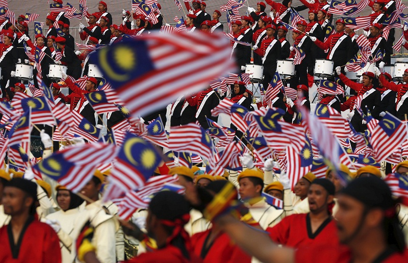 Performers wave Malaysian national flags during National Day celebrations in Kuala Lumpur, Malaysia, August 31, 2015. Malaysia's Independence Day celebrations took place on Monday, a day after thousands of protesters took part in the second day of a rally organised by pro-democracy group Bersih in Kuala Lumpur calling for electoral reform and PM Najib Razak's resignation over a multi-million-dollar payment into an account under his name. REUTERS/Olivia Harris